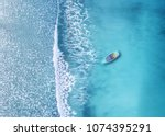Stock photo wave and boat on the beach as a background beautiful natural background at the summer time from air 1074395291