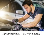 Auto mechanic working under car hood in repair garage - stock photo