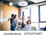 office workers are in friendly... | Shutterstock . vector #1074474407