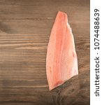 Small photo of River Trout Fillet on Wooden Rustic Background Top View