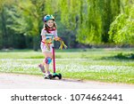 child riding scooter. kid on... | Shutterstock . vector #1074662441