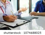patient sitting with doctor for ... | Shutterstock . vector #1074688025