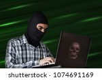 the bandit hacking the data in... | Shutterstock . vector #1074691169