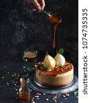 Small photo of Pear chesecake with caramel and caramel drop in black background