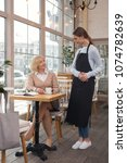 Small photo of Best service. Charming young waitress talking with her client and her client drinking coffee