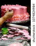 decorating a cake pink icing... | Shutterstock . vector #1074824984