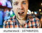 caucasian young male eating... | Shutterstock . vector #1074869201