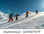 mountaineers walking up along a ... | Shutterstock . vector #1074877079