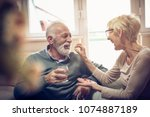 senior woman giving her husband ... | Shutterstock . vector #1074887189