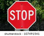 A Red Stop Sign With Trees In...