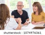 senior couple shaking hands... | Shutterstock . vector #1074976361