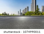 empty road with modern business ... | Shutterstock . vector #1074990011