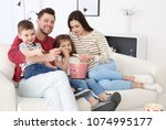 family watching tv on sofa at... | Shutterstock . vector #1074995177