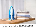 stack of clean clothes and iron ... | Shutterstock . vector #1075066757