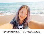 smiling young woman taking... | Shutterstock . vector #1075088231