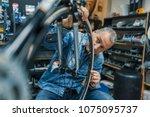 bike mechanic repairing a wheel.... | Shutterstock . vector #1075095737