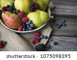 pears and mixed berries on... | Shutterstock . vector #1075098395
