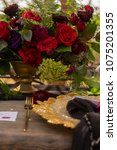 Small photo of A red rosebud, lying on a golden platter next to a black veil, a golden fork and flowers on an old wooden table. Decoration, gothic wedding. Copy space.