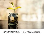 a glass jar full of coins and... | Shutterstock . vector #1075223501