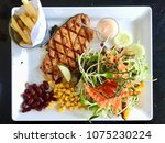 salmon steak and salad in white ... | Shutterstock . vector #1075230224