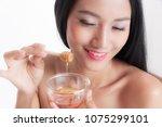 woman holding honey removing...   Shutterstock . vector #1075299101