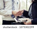 Small photo of Businessman and Businesswoman shake hands holding tablet, mobile phone in her hand after business meeting closeup. greet or thanks gesture, partnership approval, dealing, greeting and partner concept.