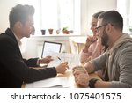 Small photo of Interior designer discussing apartment renovation idea with happy couple at meeting, smiling customers consider mortgage investment loan or flat purchase consulting realtor showing architectural plan