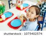 pretty asian girl sitting at... | Shutterstock . vector #1075402574