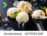 Stock photo ice cream scoops with ice cubes lemon and orange slices mint and scoop on black background 1075451369