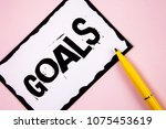 Small photo of Handwriting text Goals. Concept meaning Desired Achievements Targets What you want to accomplish in the future written on White Sticky note paper on plain Pink background Pen next to it.