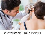 doctor checking patients ear... | Shutterstock . vector #1075494911