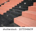 Small photo of Old Fashioned Sports Seating - Hard concrete bleacher seats in an outdoor sports facility.