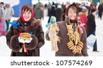 Happy girls in russian traditional clothes with pancake and doll during  Shrovetide - stock photo