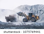 Small photo of Excavator loading dumper truck with sand at a sand quarry