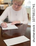 Small photo of Senior Woman Signing Last Will And Testament At Home