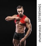 Small photo of Cute young sports man in red t-shirt shows relief abdominal muscles in gym