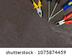 Small photo of set of hand tools nippers pliers three screwdrivers upper right corner set home master copy space holiday day father