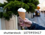 a girl is holding a white ice... | Shutterstock . vector #1075955417