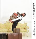 Small photo of Man with beard and mustache wearing classic suit delivers luggage, luxury white interior background. Butler and service concept. Macho, elegant porter carries heavy pile of vintage suitcases.