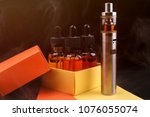Small photo of Electronic cigarette and vape liquids into opened gift box on fogged dark background. Toned light