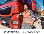 Small photo of Truck driver in front of his freight forward lorry looking at camera