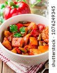 Small photo of Turkey stew with bell peppers, green beans and tomatoes in bowl on dark wooden table. Selective focus.