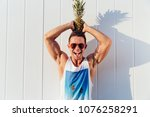 Joyful handsome man in sunglasses holds a pineapple on his head, looking at camera and smiling, wearing stylish singlet. Outdoors.
