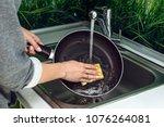 female hand washing frying pan...