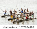 Small photo of Syuru, Asmat Region/ Indonesia - November 9 2012: When a ship visits, the warriors of the village make a mock attack in canoes, before allowing the passengers to come ashore and visit the village
