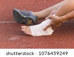Small photo of Male athlete applying compression bandage onto ankle injury of a football player, Sports injuries.