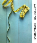 Small photo of Yellow waist measurement band on a blue wooden background.