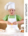 Boy with chef hat preparing the dough - breaking the eggs in the flour pile - stock photo