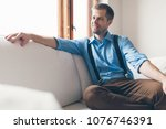 Small photo of Man sitting and relaxin on sofa at home