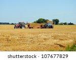 tractors load bales of hay in...